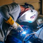 Auto worker welding a vehicle